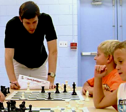 INstructor teaching chess to kid